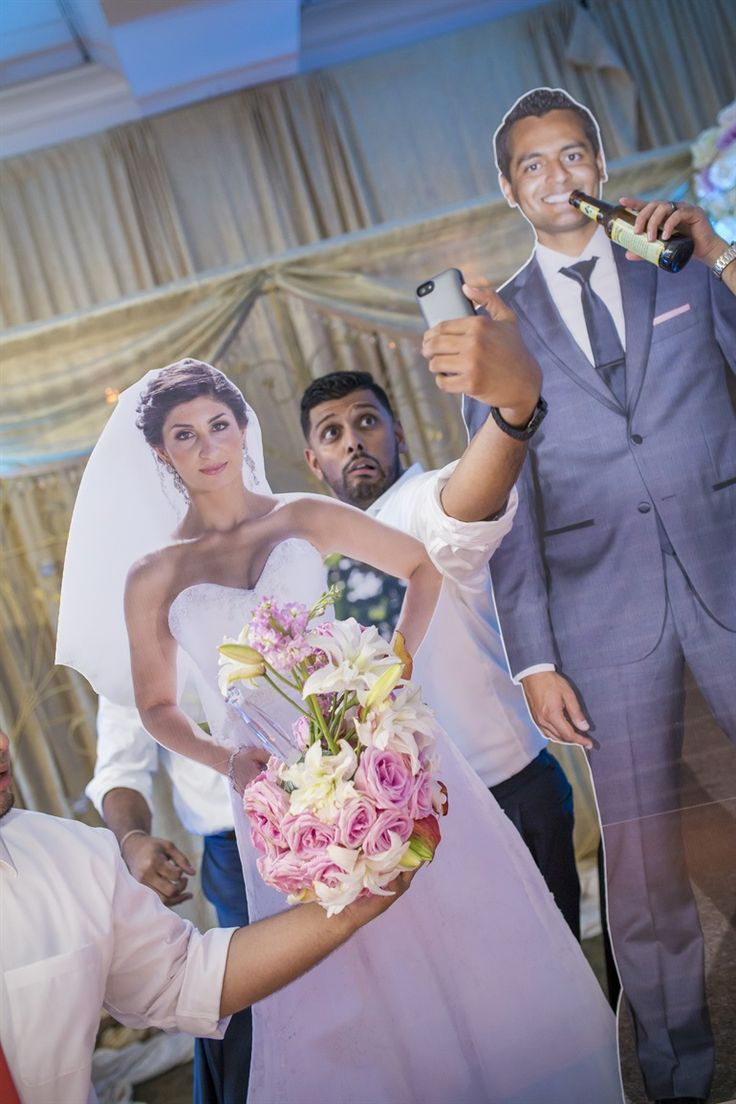 """Brilliant wedding reception idea: Friends took a photo of the couple at the wedding, then had them blown up to life size cardboard cutouts.  And they passed around the """"couple"""" to take hilarious photos."""