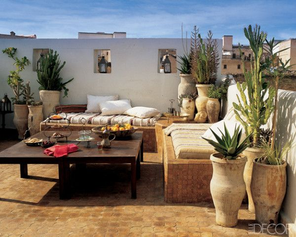 On the roof terrace of Stephen di Renza's vacation house in Fez, Morocco, mattresses are placed on tiled platforms and covered with weavings traditionally worn by shepherds. The tables are made of lacquered iron, and vintage handthrown jars, which originally stored food, now hold cacti and other indigenous plants.