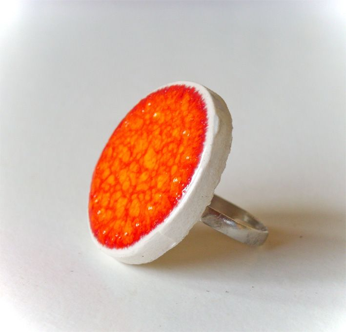 This handmade and colorful orange ring is modeled by hand in white clay.