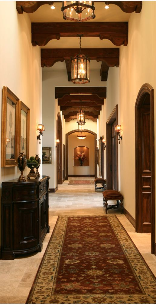 Entrance hall with beams and ceiling corbels. Also known as soffit corbels, these wooden brackets add grandeur to a long hallway. You can find similar wooden corbels at www.buycarvings.com