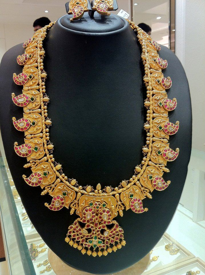 Gold necklace with ruby studded mangoes, mango and duck pendant studded with rubies