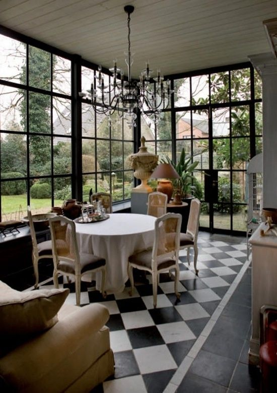 Sunroom with checked floors, floor to ceiling windows, chandelier, view of boxwoods