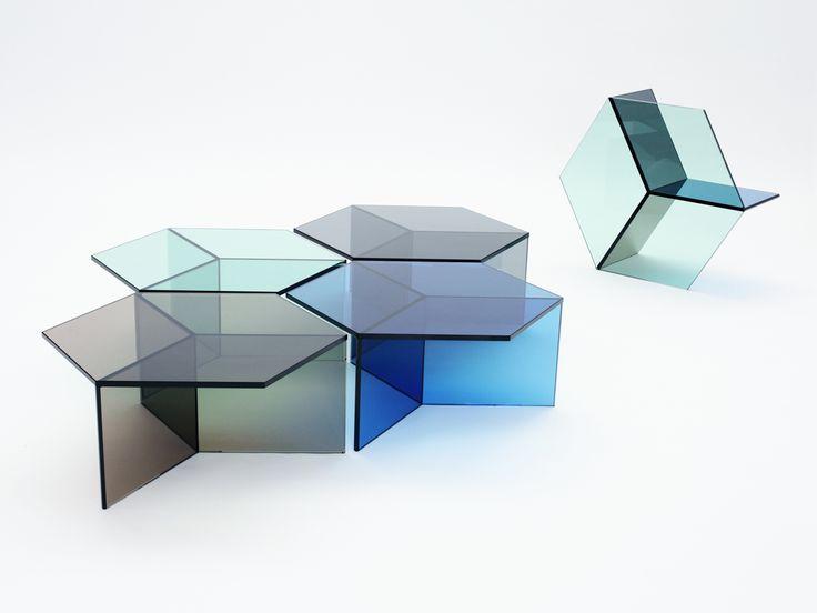 Sebastian Scherer Isom - Die Glastische von Sebastian Scherer spielen mit der optischen Wahrnehmung und wirken wie kubistische Körper. Die Tische sind aus 10 mm starkem farbigen Glas in blau, grün, grau und bronze. Die Konstruktion ist so simpel wie raffiniert. Eine sechseckige Platte liegt auf drei Rechtecken, die senkrecht in der Mitte zusammenlaufen. Die dunkel reflektierenden Schnittkanten bilden rautenförmige Flächen, sodass die isometrische Darstellung eines Würfels entsteht.