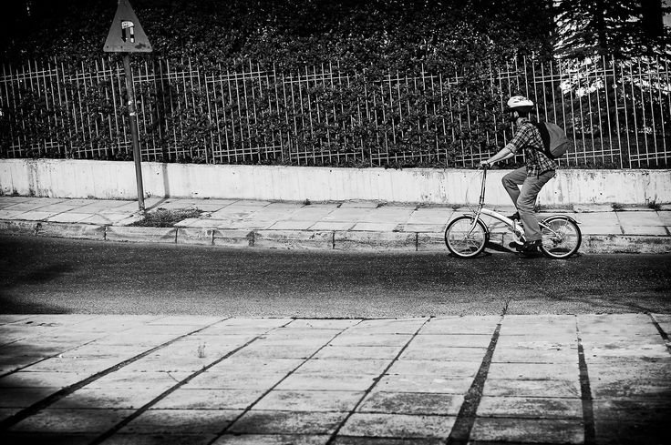 Cycling up the hill This is another one of my Athens shots, while sitting on the back of a bike. I took this one of this cyclist cycling up this not so steep hill, because he looked interesting on his tiny little bicycle. I like shooting moving objects and I found that doing so while on a moving vehicle was quite challenging, making the anticipation of a well timed shot even more intense for me.