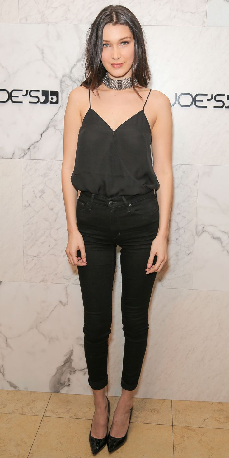 Bella Hadid in a silky black cami tucked into a pair of black skinnies. The finishing touches? A chain metal choker and patent black pumps. LOVE!