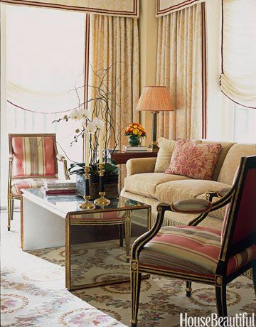 In the living room of a Chicago apartment by designer Alessandra Branca, antique armchairs are covered in a red and olive green stripe—a palette perfectly suited for fall.