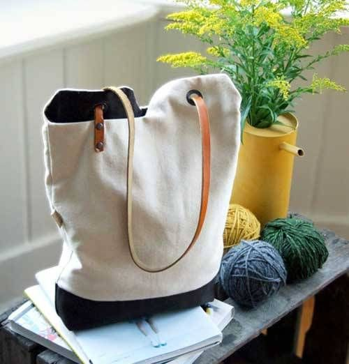 This tote bag is very simple in design and is made using white cotton canvas and brown cotton fabric. The leather strap is creatively designed to give free