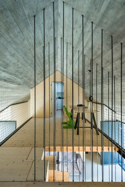 """""""We wanted the upstairs gallery that connects the two bedrooms to be as open as possible,"""" principal Aljosa Dekleva says.""""The rope mesh works as a fence for security, but is also performs as a multifunctional transparent wall on which one can hang different objects."""" Courtesy of Janez Marolt."""