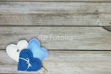 Collage of three fabric hearts on wood background