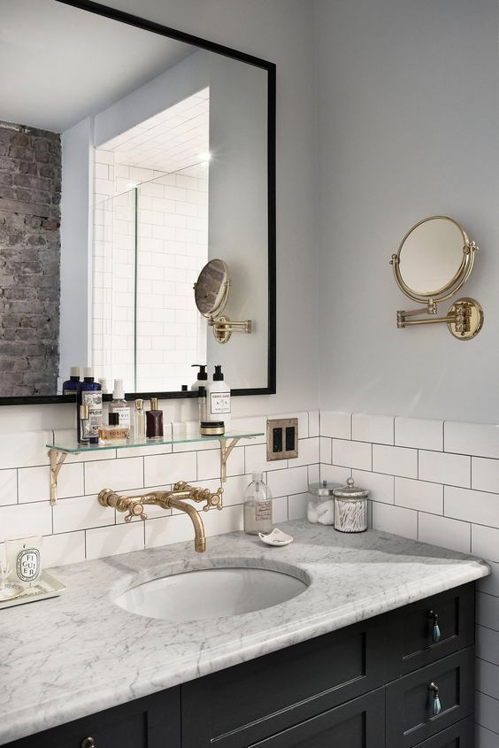 wall mounted faucet with marble counters and white subway tile