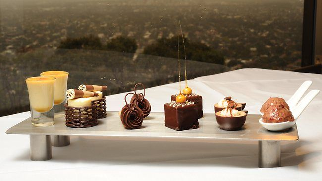 Plate of chocolate desserts at Windy Point Restaurant. L-R: white chocolate and butterscotch brulee, white chocolate cheesecake, chocolate mousse cornetto, hazelnut chocolate palet, mocha panna cotta and glace cherry and chocolate parfait.