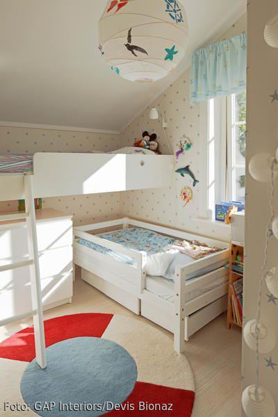 Der Platz im kleinen Kinderzimmer für Zwei kann mit einem Hochbett optimal genutzt werden – trotz Dachschräge. Damit sich das Kind im unteren Bett etwas freier fühlt, hilft es, das Einzelbett quer zum Hochbett zu stellen, sodass das Kopfende herausguckt. Weiße Möbel und helle Tapeten lassen den Raum außerdem etwas geräumiger wirken.