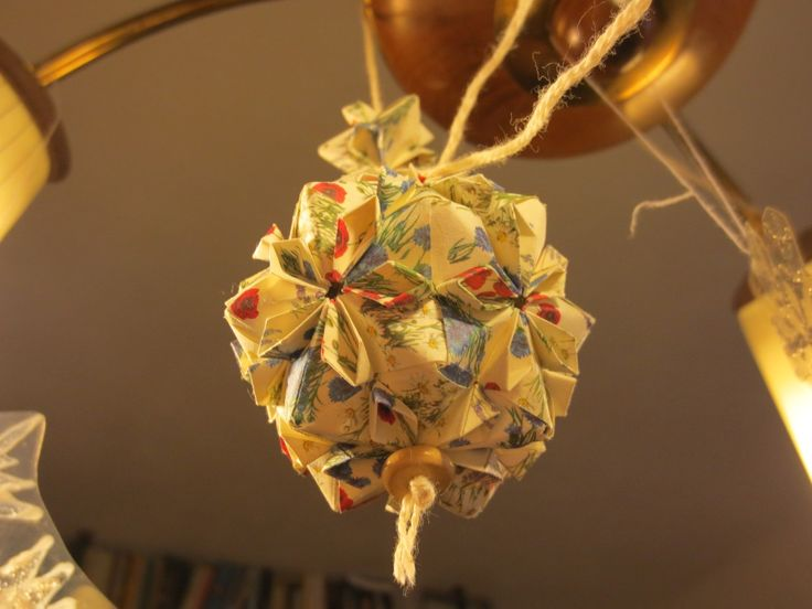 cherry blossom kusudama with meadow flowers on the paper - geometrically it's an icosahedron with tetrahedrons on each side of it