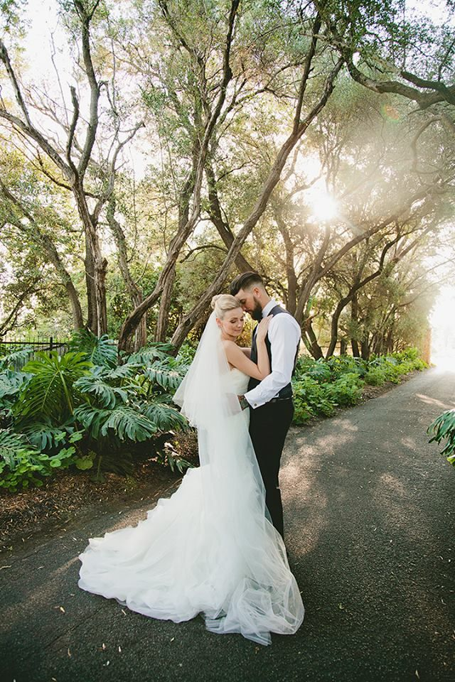 Whimsical bride and groom wedding day photo shoot. Under trees and wearing ivory strapless gown. Groom wearing navy suit and tan shoes.