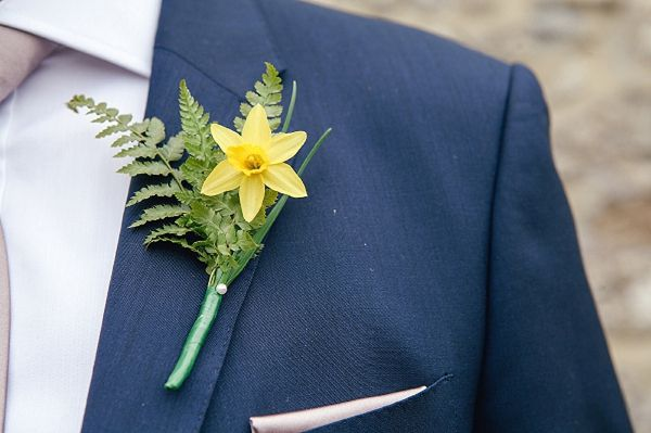 The guys have an emerald paisley bowtie and a white pocket square with black tuxes. The daffodil looks a little too small, so I would maybe have two there with the greens.