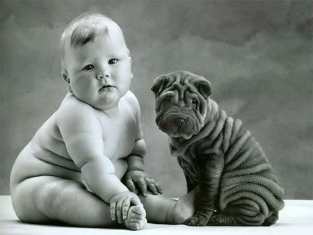 Black wrinkled puppy sitting with a wrinkled baby.. Follow the pic for more awww