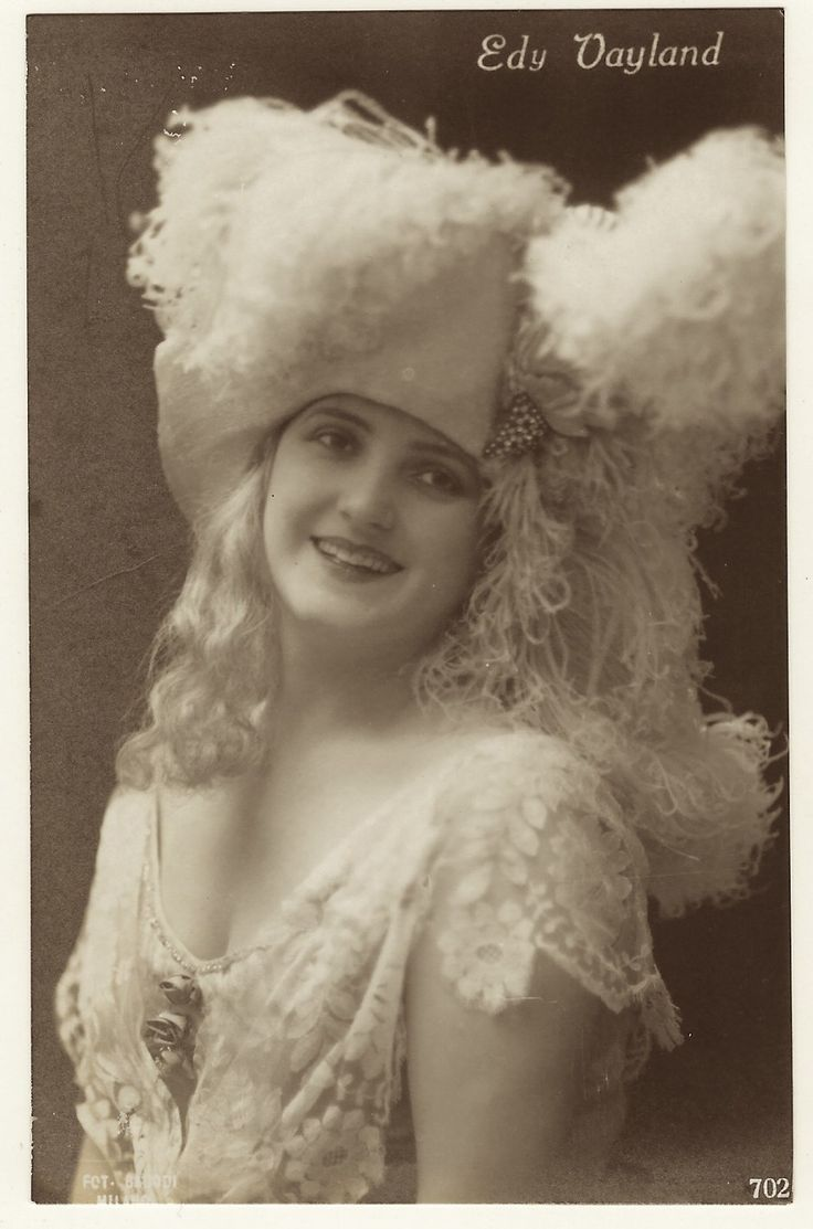 The pretty costumed blonde actress featured in this real photo postcard is Edy Vayland. She is wearing a fantastic headdress and this portrait is a bit risque. Preliminary research revealed zero in…