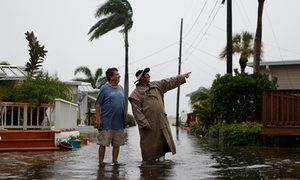 Residents survey the rising water coming from the Gulf of Mexico into their…