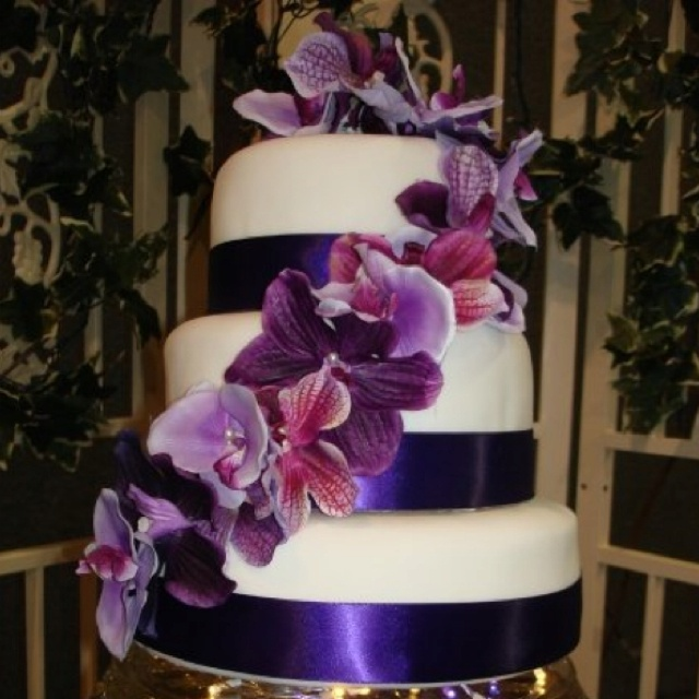 Simple wedding cake decorated with silk orchids and satin ribbon