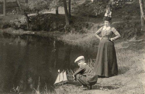 Een vrouw en een jongetje bij een vijver [waterplas]. De vrouw staat met haar handen in de zij. Zij draagt een frivole hoed, een donkere lange rok en een blouse met lange mouwen. De kraag en manchetten zijn van kant. Het jongetje zit op zijn hurken bij de waterkant en speelt met een zeilbootje [tweemaster]. Hij draagt een donker pakje en een pet. In, of in de buurt van, Baarn, ca. 1905 [Bromidedruk, 9,8 x 15,1 cm]