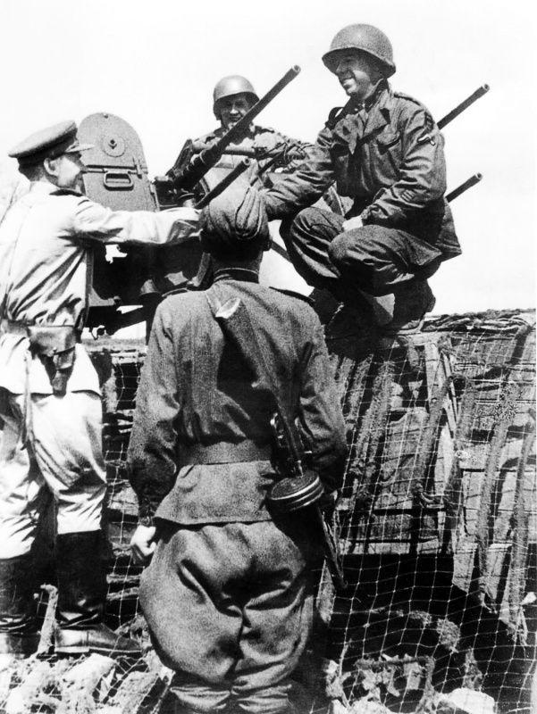 Советские и американские солдаты беседуют возле зенитных пулеметов «Браунинг» в Торгау.