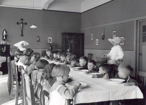 Katholieke Charitatieve / liefdadigheids-instellingen: kinderen aan tafel (weeshuis?) krijgen te eten van de Zusters van de Heilige Vincentius (communiteit van de Dochters der Liefde) [Zusters van St. Vincentius A. Paulo]. Nederland, [Tilburg], [1940].