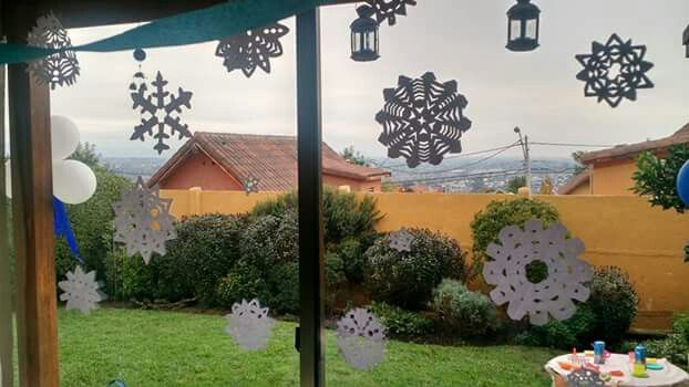 Copos de nieves de papel pegados en la ventana.