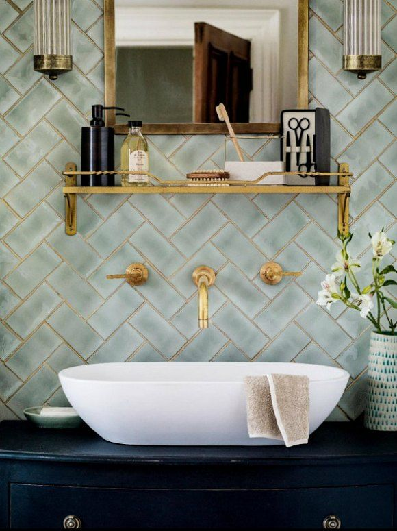 A white wash basin resting on a dark vanity cabinet, against a light blue-green tile laid in a herringbone pattern, with brass grouting, a brass faucet, brass shelf, brass mirror and brass sconces on either side of the mirror.