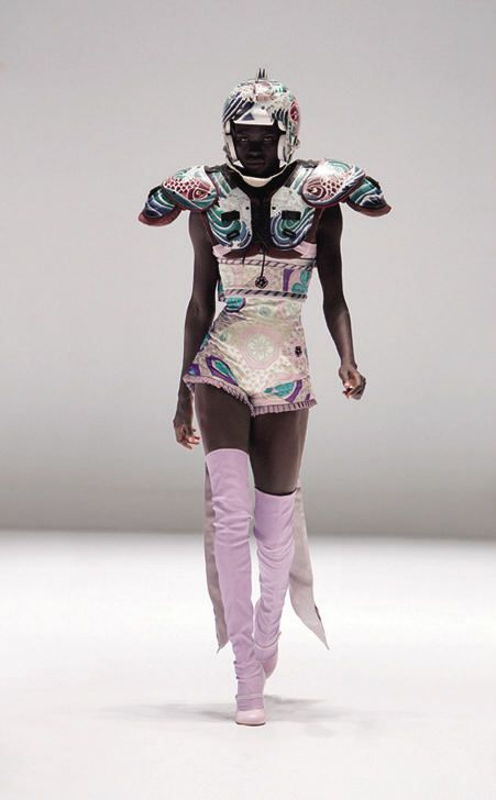 .Bodysuit and obi-style sash of lilac silk satin and chiffon embroidered with silk thread; shoulder pads and helmet of fiberglass painted with acrylics  Courtesy of Alexander McQueen