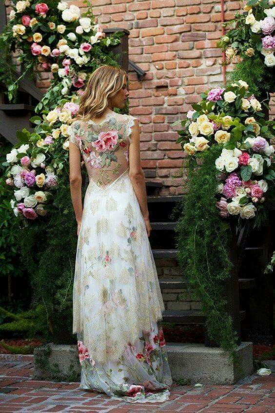 We are obsessed with the floral pattern and gold lace applique detail on this dress. What a unique look for a wedding dress.