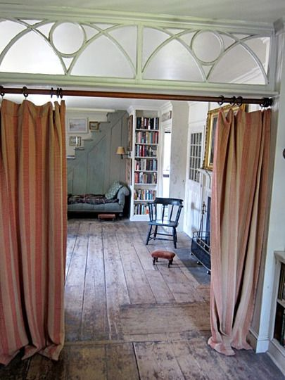 I love the slightly sloppy striped curtains dragging on the old ship floor with the great trim on top.  You almost feel like you're going back stage at the circus or a vaudeville theater. It doesn't hurt that 'back stage' is a blue lounge for reading great books under the stairs :)
