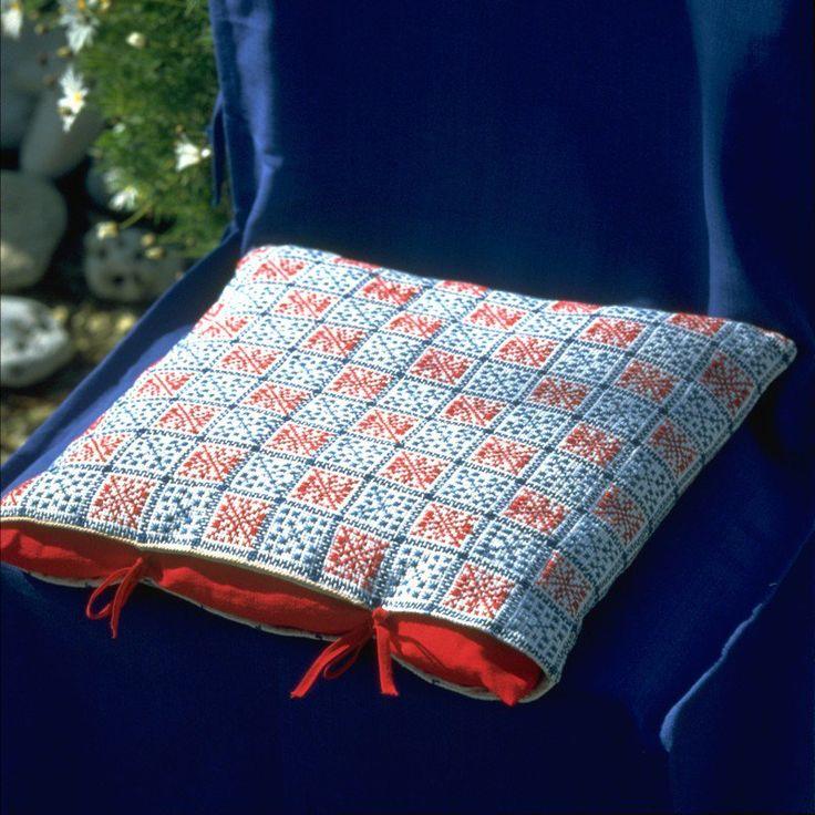 Une housse de coussin brodée au point de croix en bleu et rouge