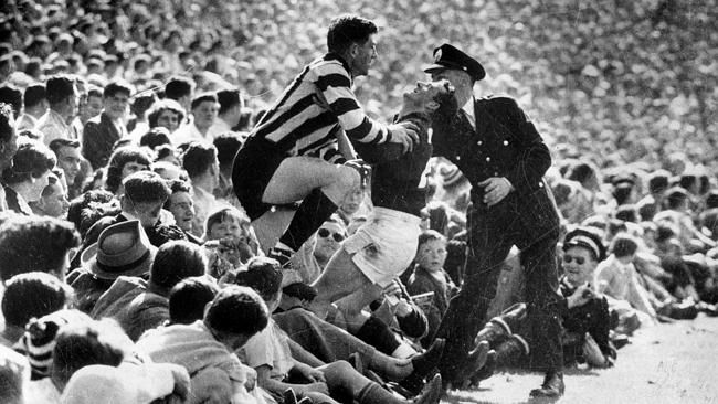 1956: MCG crowd spills on to boundary; fans get a close look at Neil Mann and Ian Ridley in the Melb v Collingwood Grand Final