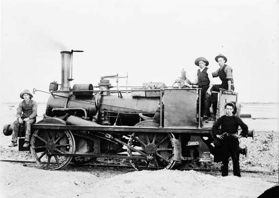 The Melbourne & Hobsons Bay Railway Company opened Australia's first steam railway when public services began on 12 September 1854 on its short 2¼-mile (3.6 km) line connecting Melbourne with a deepwater pier at Sandridge (later Port Melbourne) on Hobsons Bay. Pictured here is the Hobsons Bay steam locomotive with staff.