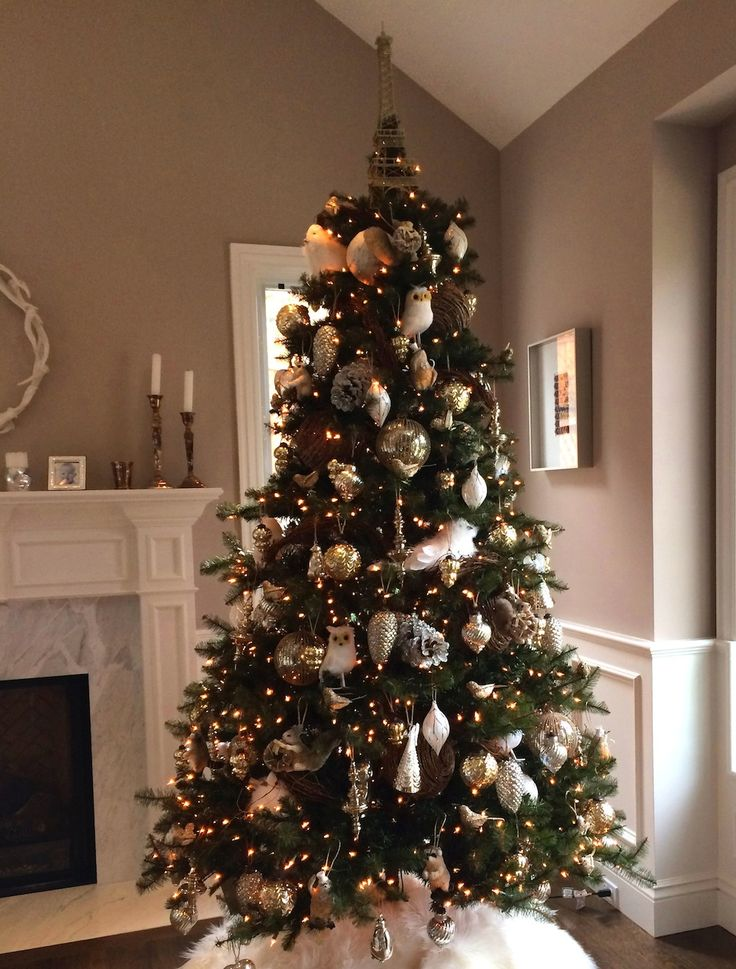 A Pottery Barn Christmas Tree With All the Trimmings Wicker garland, birds, large bear, skirt is white fir...love it