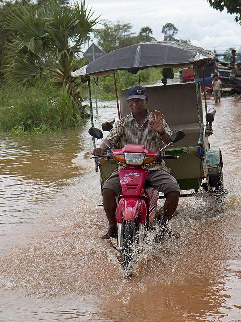 A tuk-tuk taxi drives through floodwater near the Tonlé Sap lake, Cambodia