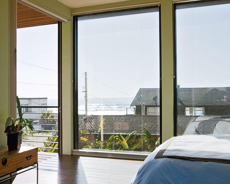 В спальне большие окна от пола до потолка открывают вид на океан.  (пляжный,индустриальный,лофт,винтаж,стиль лофт,индустриальный стиль,современный,архитектура,дизайн,экстерьер,интерьер,дизайн интерьера,мебель,спальня,дизайн спальни,интерьер спальни) .