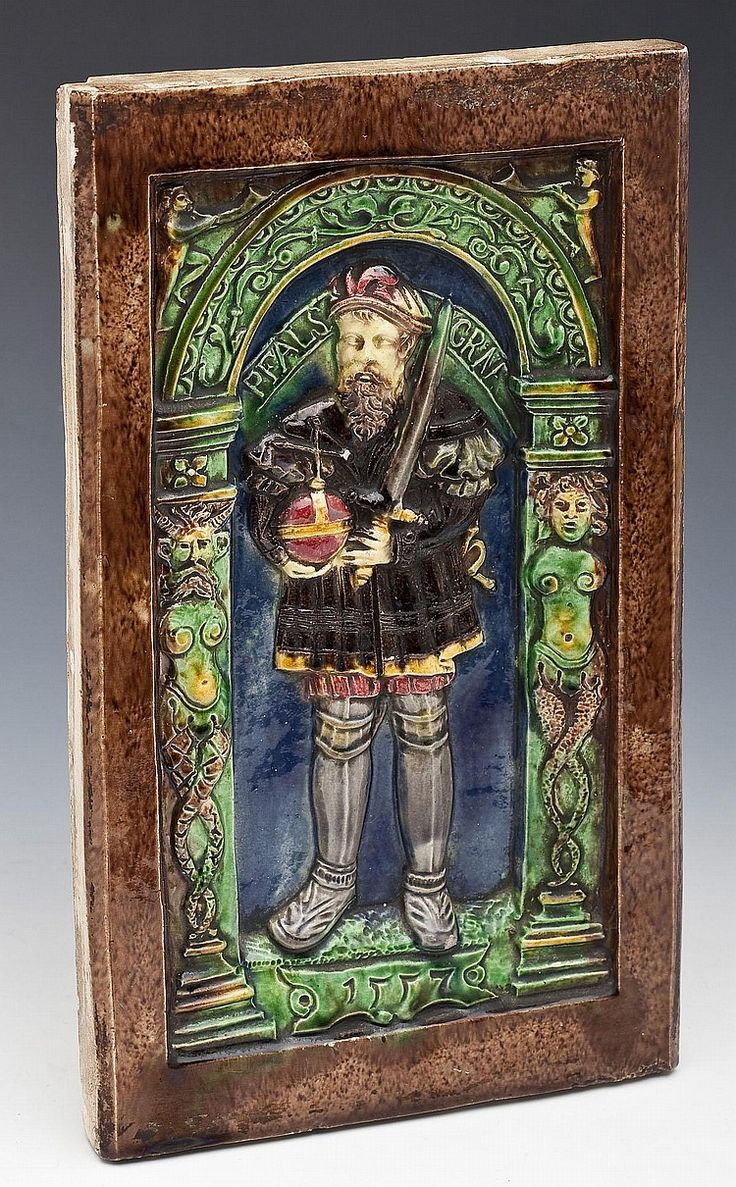 """DESCRIPTION: 16th century ceramic German stove tile with figure of a bearded gentleman wearing a colorful tunic and holding globus cruciger and a sword. Figure standing in archway supported by columns depicting a merman and a mermaid. """"1557"""" carved on front. Color palette mainly green and brown with yellow and red accents. MEASUREMENTS: 12-3/4"""" x 7-1/2"""" x 1"""". CONDITION: Minor roughness along top right edge, two minimal chips to surface of figure, significant chip on two corners."""