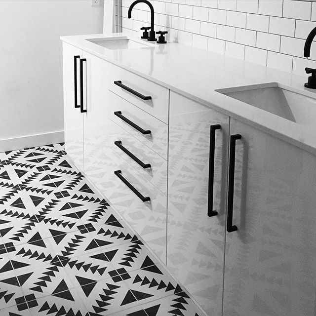 Black and white encaustic tile, matte black fixtures, white vanity.