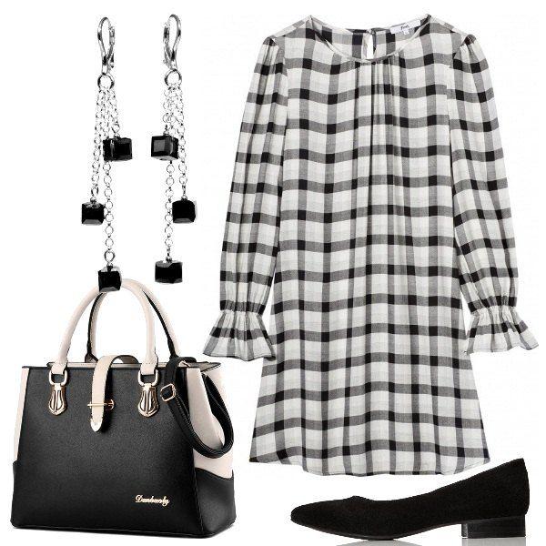 Un vestito corto a scacchi bianchi e neri, con le maniche lunghe, viene proposto con un paio di ballerine con un piccolo tacco. La borsa a mano è bicolore e gli orecchini hanno dei piccoli pendenti neri, a forma quadrata come gli scacchi.