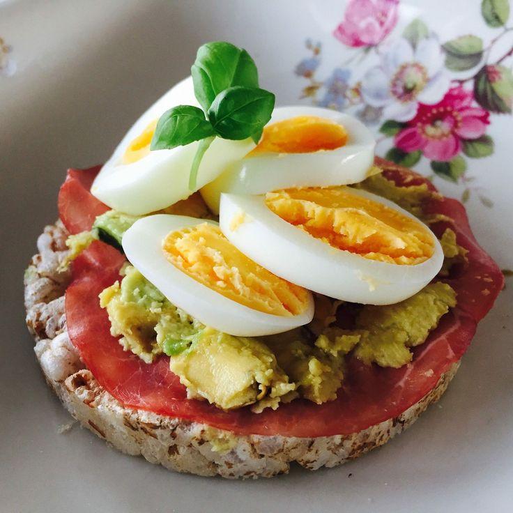 Breek de dag, tik een eitje. Ontbijt van rijstwafels met avocado, ei en rookvlees.