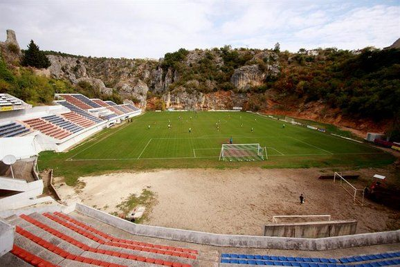 Gospin Dolac - Croatia  There is nothing more remarkable about this 4,000 seater stadium in Croatia other than where it's situated.  Nestled at the top of a mountain it is surrounded by cliffs, a 10th century fortress and 500m deep blue lake.