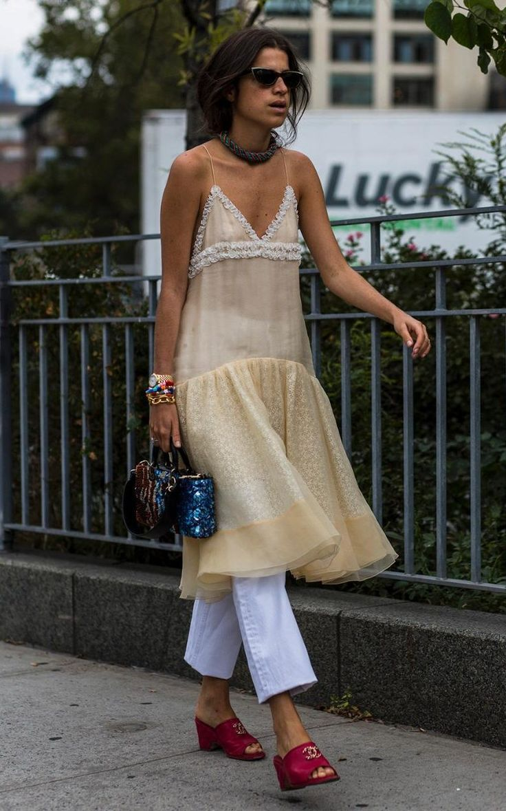 Leandra Medine tried out the dress-over-trousers trend with an embellished slip and white jeans.