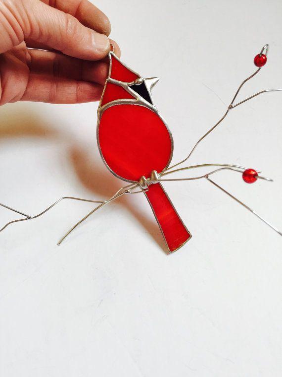 Belle suncatcher cardinal rouge fait avec un verre transparent semi rouge vif, il est assis sur une branche de fil ornée de verre rouge «baies» les branches fan en les éloignant de la fenêtre donnant à cette pièce un effet de 3 dimensions. Une aspiration est incluse. Fait avec soin en utilisant la méthode de la feuille de cuivre traditionnel. Le cardinal lui-même mesure 5.25 x 2» et la pièce entière avec branches 8,5  x 8 .  Cet article est fabriqué sur commande et généralement expédié…
