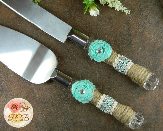 Charming burlap cake knife set is wrapped with jute string, ivory lace, Tiffany Blue rosettes and ribbon, and a little bit of bling. Made of