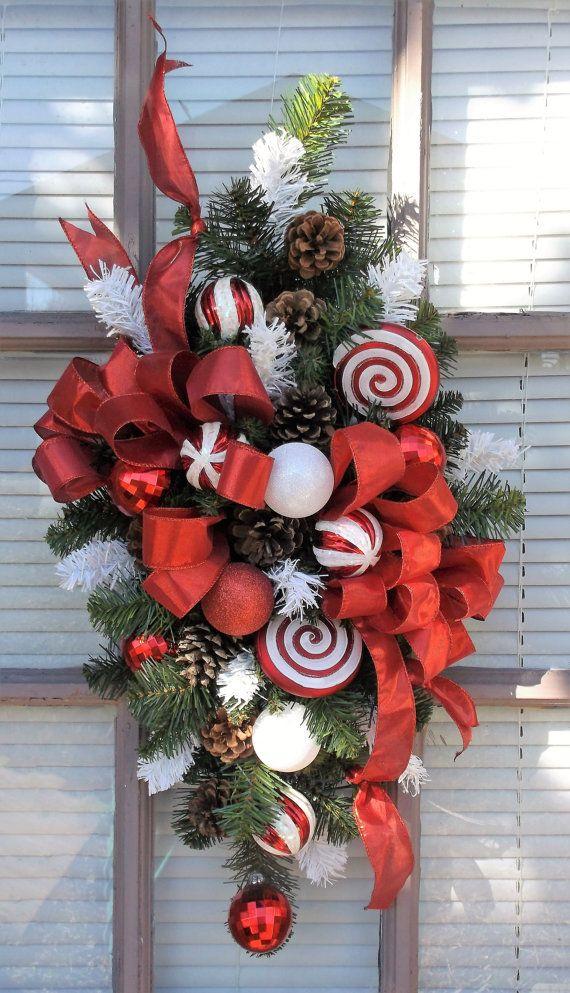 «SENSATION DE MENTHE POIVRÉE» Fête Noël porte Swag  Swag dynamique et festive artificielle mixtes conifères et blanche porte est élégamment conçu avec un grand rouge ruban, noeud avec plusieurs banderoles en cascade, pommes de pin naturel, menthe poivrée grand disque ornements, décorations de boule glacé menthe poivrée, rouge brillait ornements boule ornement, blanc glacé pour créer une belle Bienvenue pour votre famille et vos amis.  Son design polyvalent se prête aussi à étendre sur une…