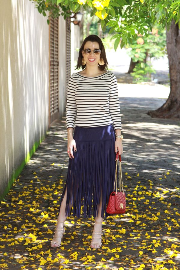 Look navy moderno com blusa listrada, saia de franjas, bolsas vermelha com alça de correntes e sandália nude