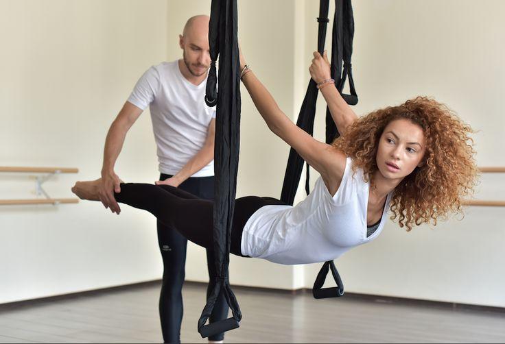 Postura in suspensie in timpul unui curs Air Yoga, ce activeaza erectorii spinali, ce sustin coloana vertebrala, precum si intreaga musculatura a picioarelor. Dificultate: usor.  Rezerva si tu o sedinta de Air Yoga pe www.airyoga.ro