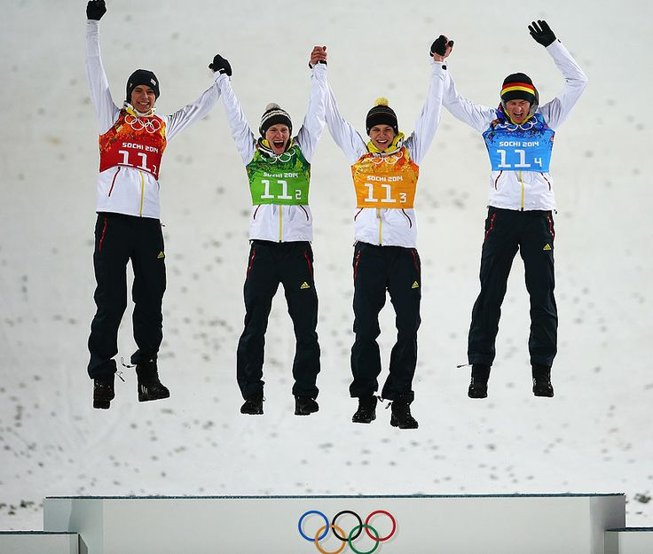 Gold medalists Andreas Wank, Marinus Kraus, Andreas Wellinger and Severin Freund of Germany celebrate during the flower ceremony for the Men's Team Ski Jumping at Sochi
