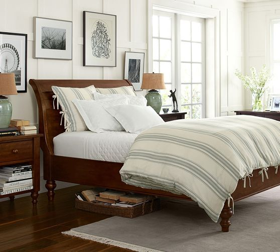 Bedding layout: neutral quilt/coveret in ivory or light gray; paired with patterned duvet at base of bed with matching euro or king sham